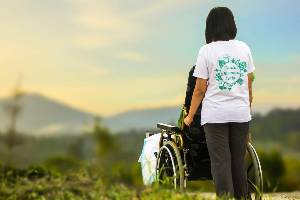 Zdjęcie przedstawia spacer po łąkach chorego człowieka na wózku inwalidzkim oraz osoby, która sie tym człowiekiem zajmuje. Obie osoby obrócone sa tyłem do aparatu, nie widac ich twarzy. Kobieta, która sprawuje opiekę nad chorym stoi za wózkiem i patrzy na krajobraz.