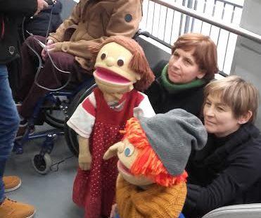 Na zdjęciu, na pierwszym planie widoczne są dwie szmaciane lalki, Tomek i Malwina. Lalka Tomek siedzi na wózku inwalidzkim. Za nimi znajdują sie dwie kucajace panie, które przytrzymują lalki. Lalki są wielkości kucającego człowieka. Na następnym planie młody mężczyzna równiez na wózku, udziela wywiadu komus trzymającemu przed nim mikrofon. Całość akcji toczy się w tramwaju.