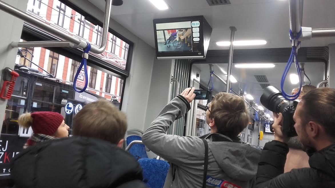 Na zdjęciu widzimy duży tłok reporterów w tramwaju, którzy robią zdjęcia, bądź kręcą spot puszczony na ekranie znajdującym sie w tramwaju. Wszyscy wokół oglądają go z zainteresowaniem.