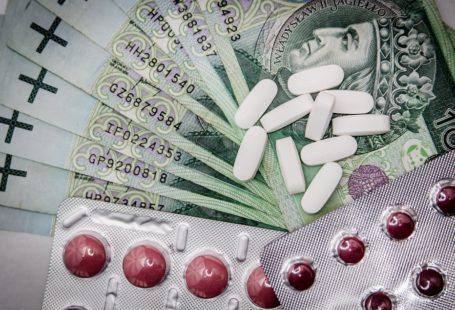 Na zdjeciu znajdują się rozłożone w wachlarz pieniądze, oraz leżące na nich różne leki. Podłużne białe bez opakowaniaiałe oraz okrągłe czerwone w opakowaniu.
