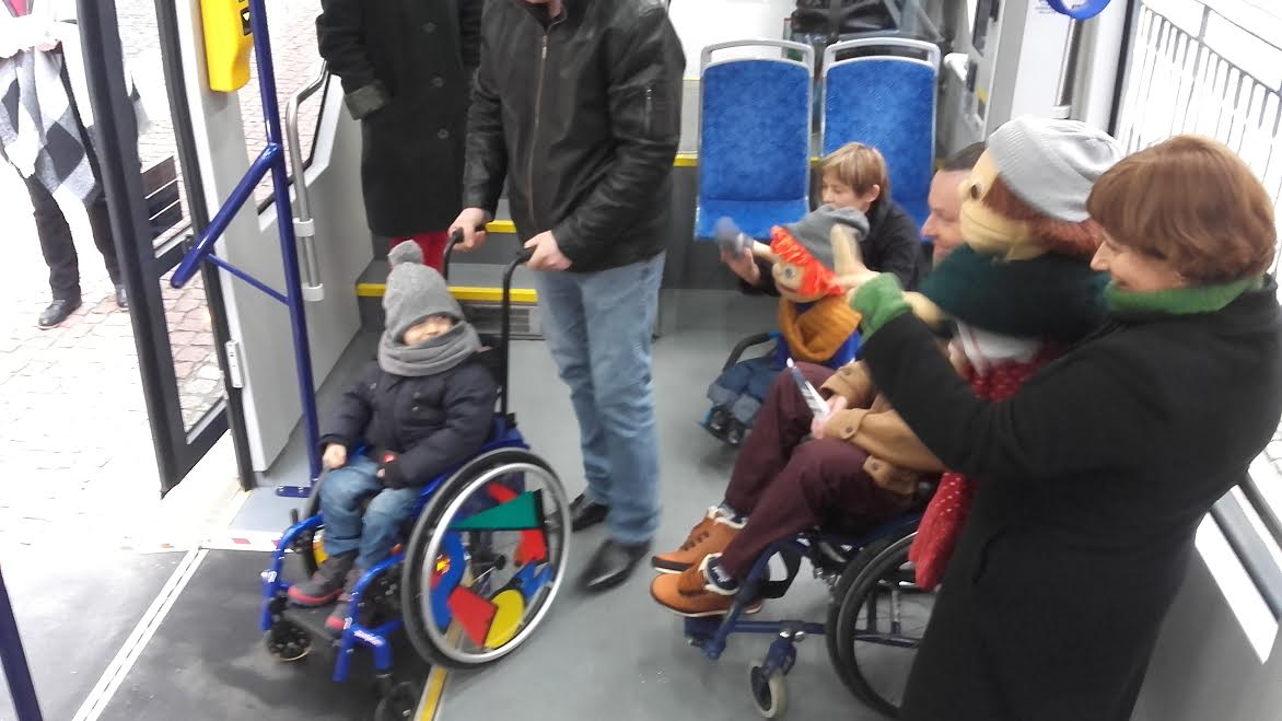 Na zdjęciu widzimy uśmiechnietego małego Patryka na kolorowym wózku inwalidzkim, wyjeżdżającego z tramwaju, na pożegnanie machaja mu lalki oraz panie trzymajace naszych bohaterów