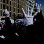 Zdjęcie przedstawia tłumnie protestujące osoby z niepełnosprawnościami w Grecji. Widoczne są tylko ich podniesione ręce, na których są białe rękawiczki. W tle widać nowoczesne budynki.