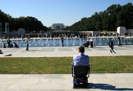 Na zdjęciu znajduje się mężczyzna odwrócony tyłem, siedzący na wózku inwalidzkim, przypatrujący się ludziom przy fontannie. Ubrany jest bardzo elegandzko, w koszulę, wygląda, jakby wyszedł dopiero z pracy.