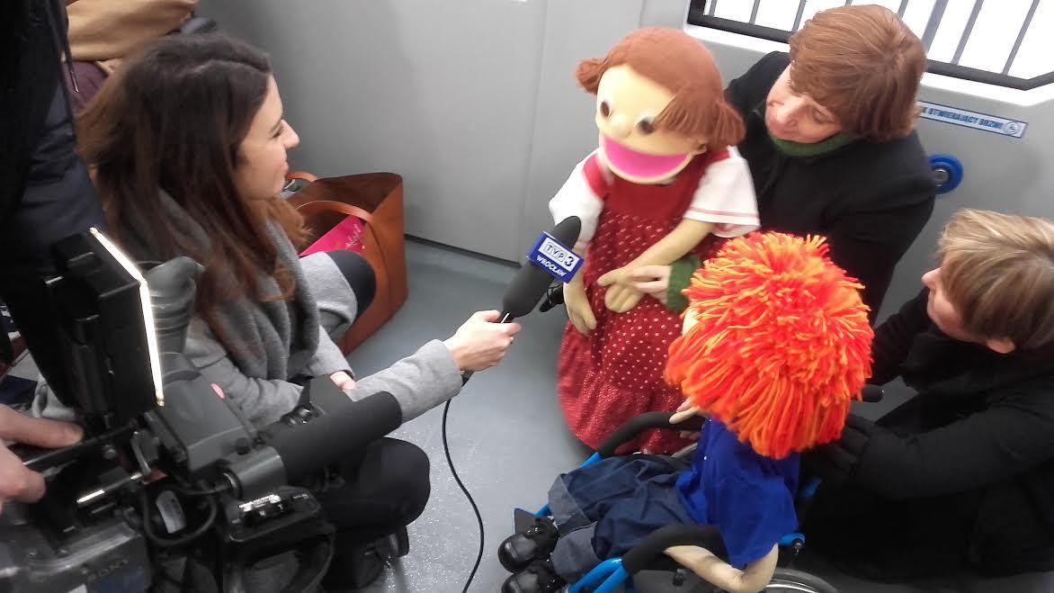 młoda dziennikarka TVP Wrocław przeprowadza wywiad z lalką Malwiną. Tomek sie jej uwaznie przygląda.