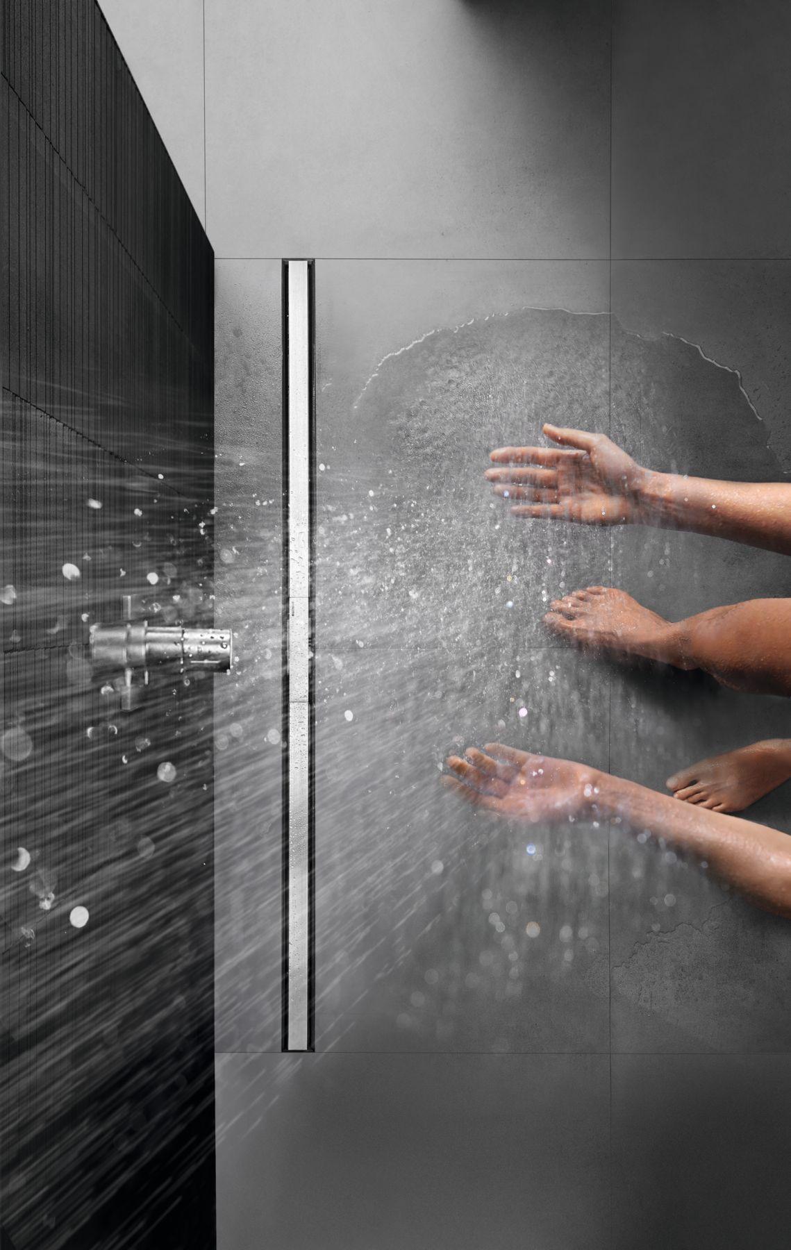 człowiek korzystający z prysznica bezbrodzikowego. Zdjecie zrobione z góry, które uchwytuje tylko wystające stopy oraz dłonie sięgające do lejącej się wody.
