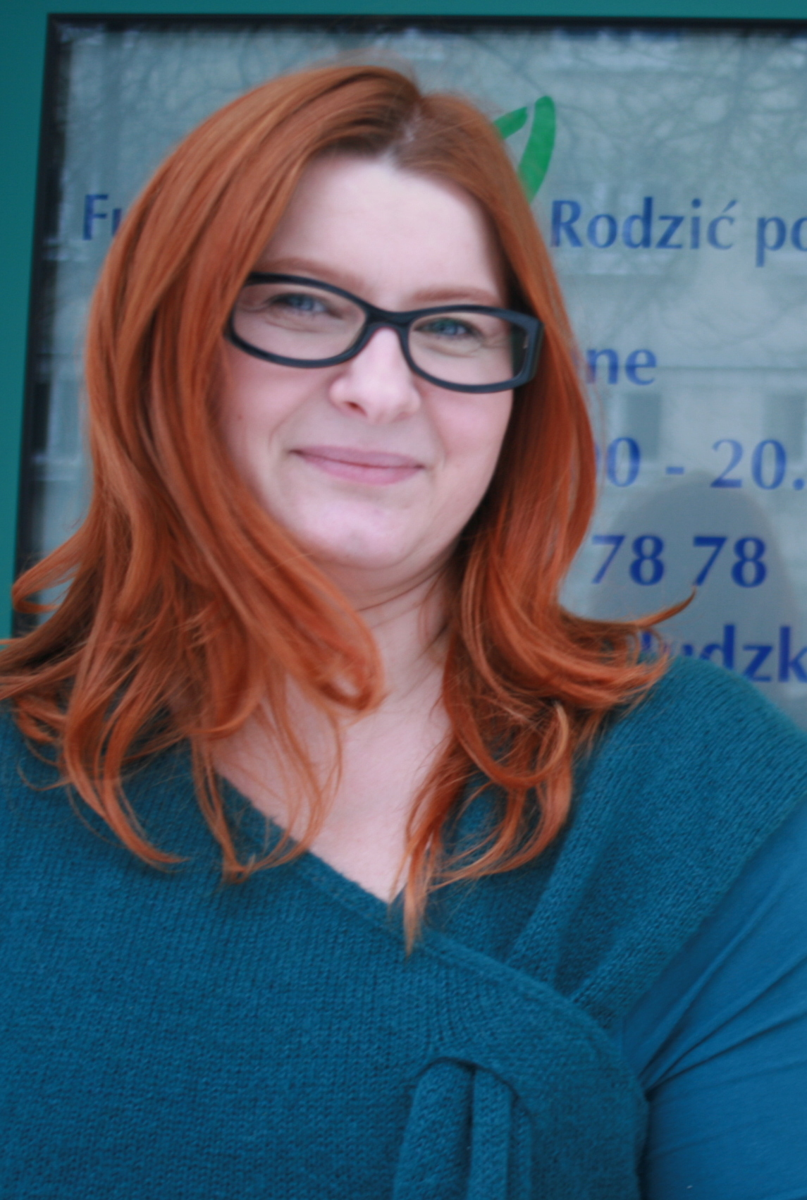 Na zdjęciu znajduje sie portret Joanny Pietrusiewicz, Prezeska Fundacji Rodzić po Ludzku. Pani Joanna na zdjęciu jest uśmiechnięta, ma na sobie okulary, niebieska bluzke oraz piękne, rude włosy.
