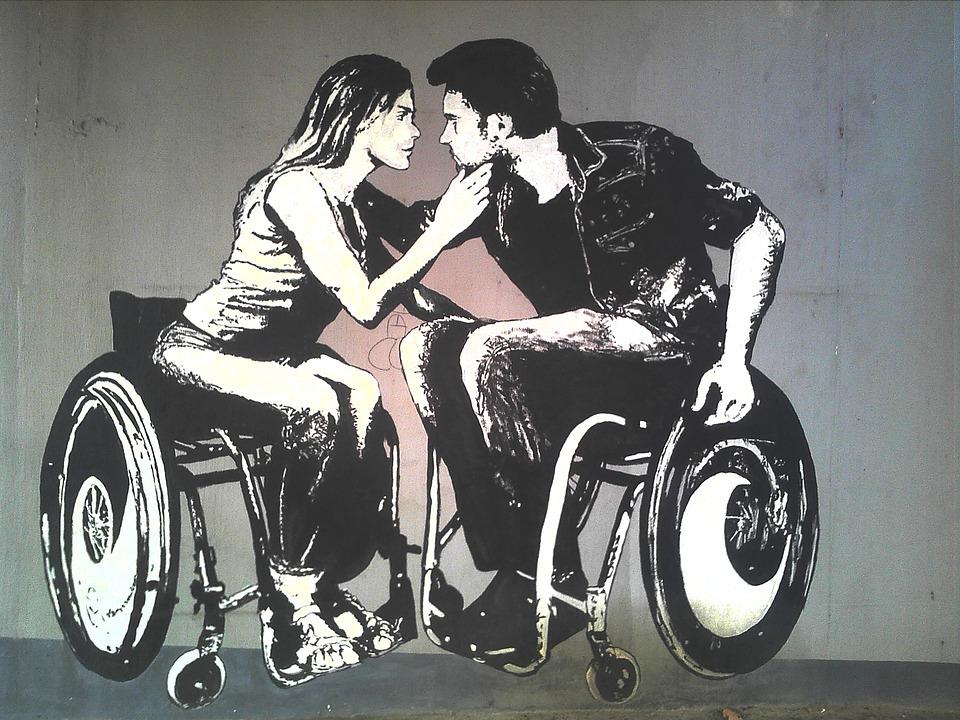 Obrazek przedstawia graffiti, na którym znajduja sie dwie całujące się osoby na wózkach inwalidzkich, kobietę i mężczyznę.