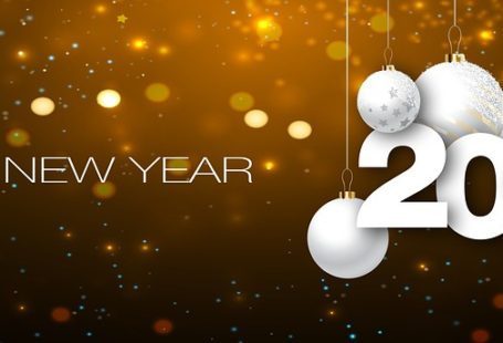 Na obrazku na złotym tle z migającymi z tyłu lampkami, znajduje się napis Happy New Year oraz zwisający wraz z białymi bąbkami rok 2017.