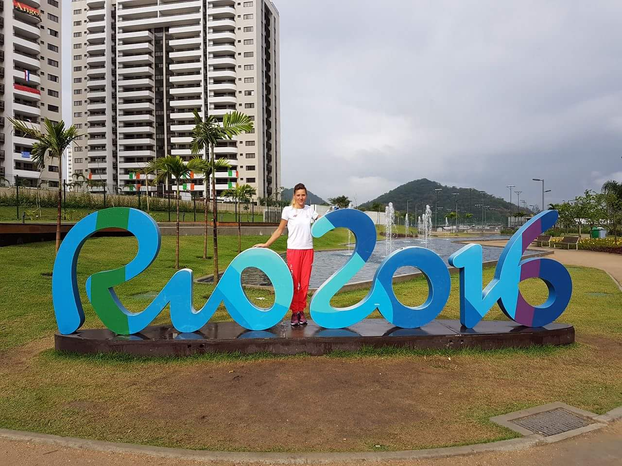 Pani Katarzyna Piekart przy niebieskim napisie Rio 2016, stojącym na ziemi. W tle widać wzniesienie i biały wieżowiec.