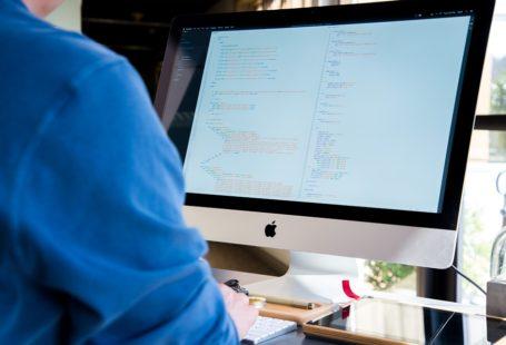 Na zdjęciu widoczny jest komputer, przed którym siedzi lekarz. Siedzi tyłem do aparatu i nie widać przez to jego twarzy.