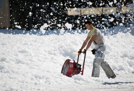 Na zdjęciu znajduje się mężczyzna pracujący na odśnieżarce spalinowej. Wyglądem i użytkowaniem przypomina kosiarkę. Wokół jest mnóstwo śniegu. Mężczyzna jest młody, ok 30 lat, ubrany jest w termoaktywne spodnie i o dziwo koszulkę z krótkim rękawem.