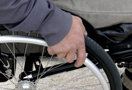 Zdjęcie przedstawia kadr dłoni mężczyzny siedzącego na wózku inwalidzkim.