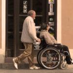 Na zdjęciu widać dwie osoby (kobietę i mężczyznę) po pięćdziesiątce, podczas spaceru po mieście. Najprawdopodobniej małżeństwo. Kobieta siedzi na wózku inwalidzkim, a mężczyzna prowadzi wózek. Patrzą w stronę witryn sklepowych.