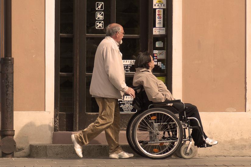 Na zdjęciu widac dwie osoby (kobietę i mężczyznę) po pięćdziesiatce, podczas spaceru po mieście. Najprawdopodobniej małżeństwo. Kobieta siedzi na wózku inwalidzkim, a mężczyzna prowadzi wózek. Patrza w strone witryn sklepowych.