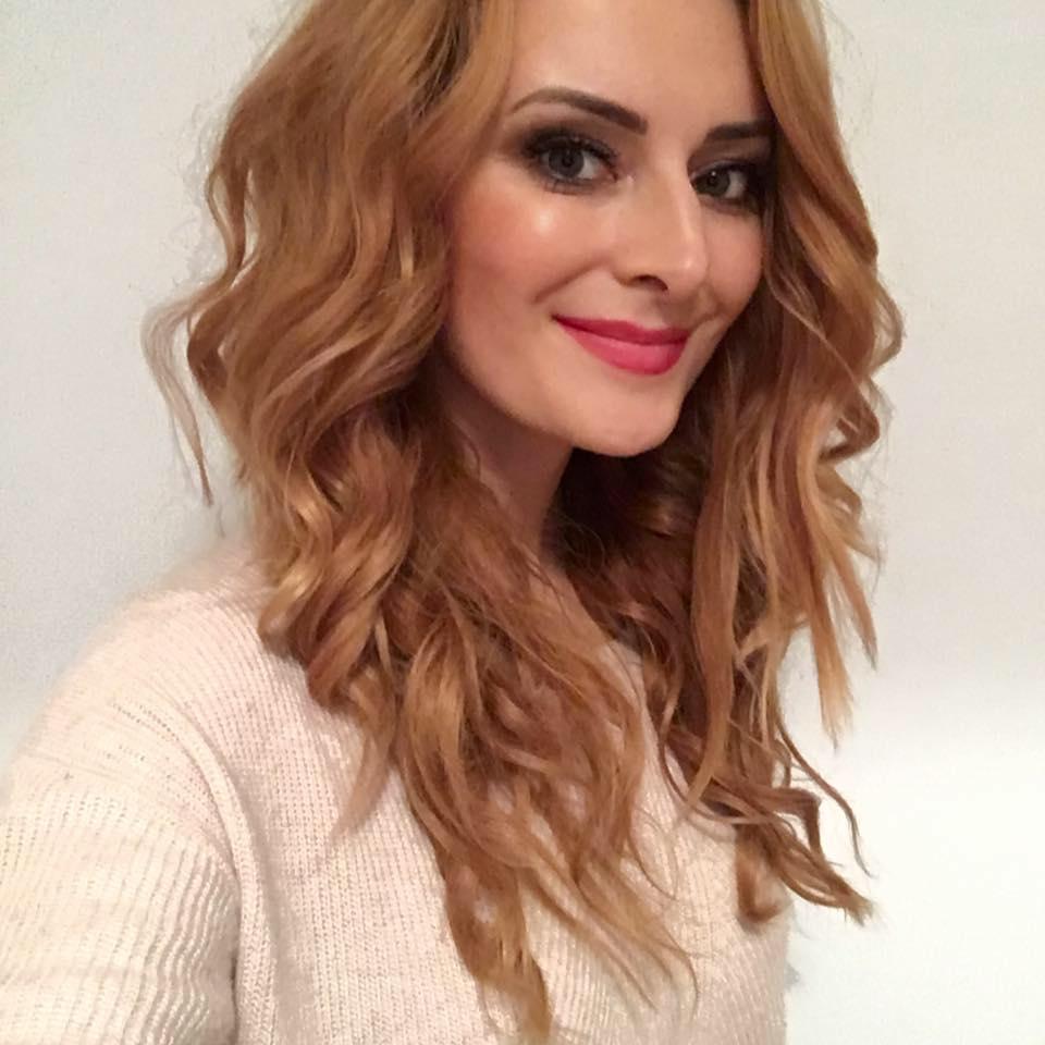 Na zdjęciu znajduje sie przepiękna Iwona Cichosz. Jest to portret. Pani Iwona ustawiona jest półprofilem, ma piękne falowane blond włosy, oraz śliczny uśmiech. Ubrana jest w beżową bluzkę.