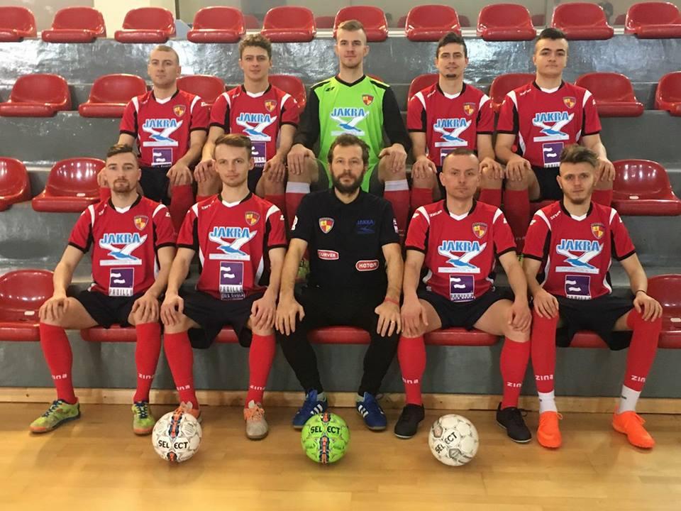 Zdjęcie przedstawia drużynę MKSN Mazowsze Warszawa. Na zdjęciu pozują siedząc na czerwonych krzesełkach trybuny w dwóch rzędach (pięć osób na górze i pięć na dole).