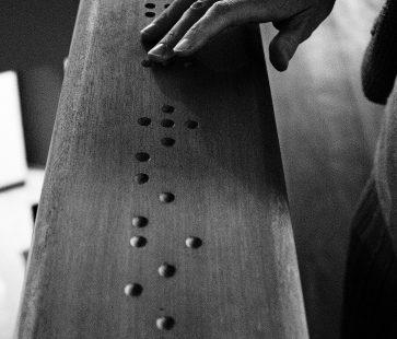 Zdjęcie przedstawia dłoń, która dotyka blatu, na którym jest wytłoczony napis w języku brajla. Zdjęcie jest czarno-białe.