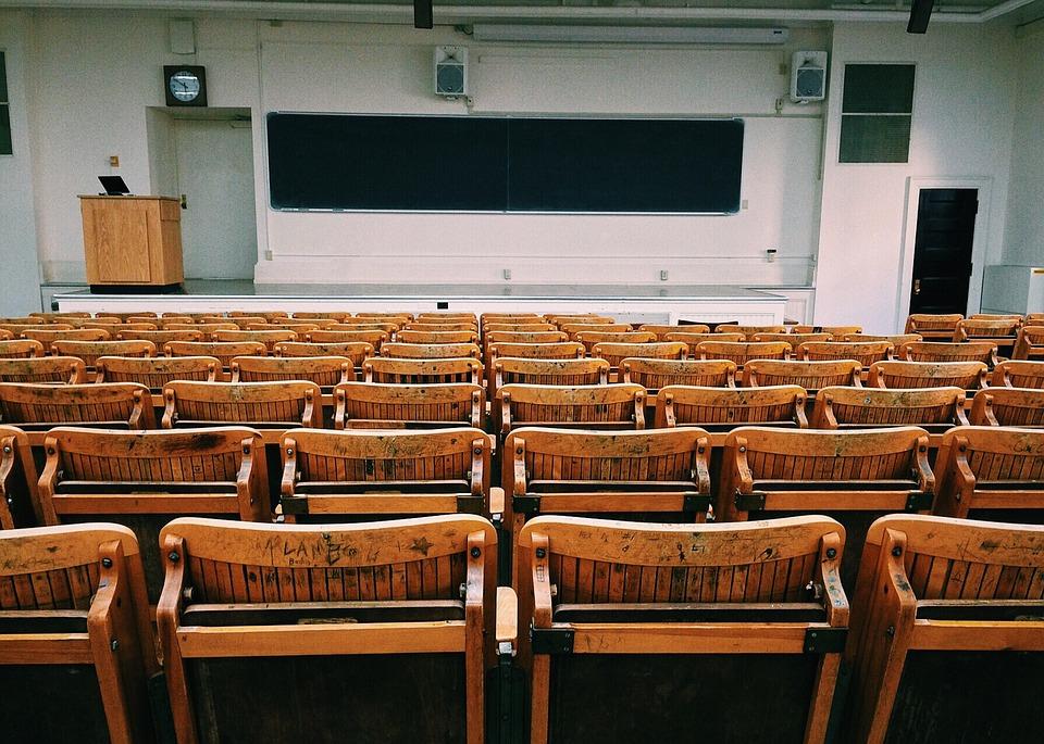 zdjecie przedstawia dużą, pustą salę wykładowa na uniwersytecie (aulę), Zdjęcie zrobione z prespektywy siedzącego studenta, na drugim planie widać tablicę, a na pierwszy złozone drewniane krzesła od tyłu.
