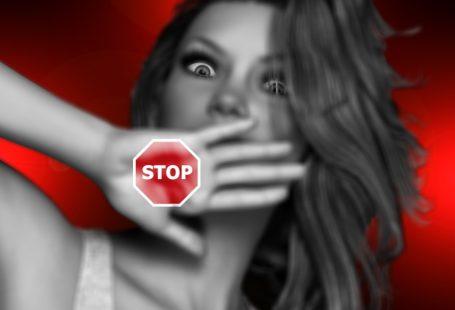 Zdjęcie przedstawia wystraszoną kobietę, zakrywającą dłonią twarz, przed domniemanym atakiem. Na jej dłoni przyklejony jest znaczek stop.