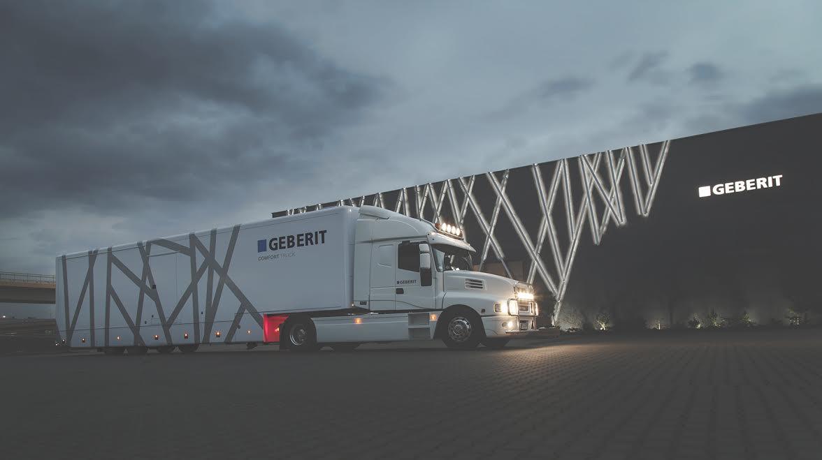 Wielki, piękny, biały samochód ciężarowy z nazwą marki geberit na naczepie. W środku tira znajdują się trzy ekskluzywne kabiny toaletowo-prysznicowe.