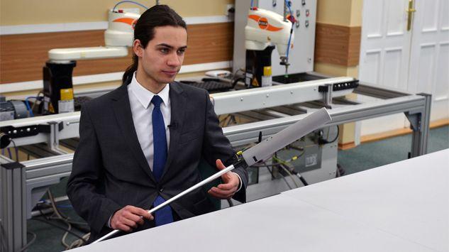 Na zdjęciu widoczny jest sam łukasz kolman - w trakcie prezentowania swojego wynalazku. Ubrany jest w ciemny garnitur, jasną koszulę, niebieski krawat, ma długie ciemne włosy spięte z tyłu w koński ogon.