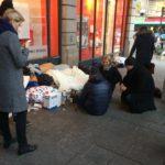 Zdjęcie Rzecznika Praw Obywatelskich w czasie spotkania z bezdomnymi w Paryżu. Zdjęcie wykonane na ulicy, parę osób stoi, a inni siedzą przy bezdomnych na chodniku.