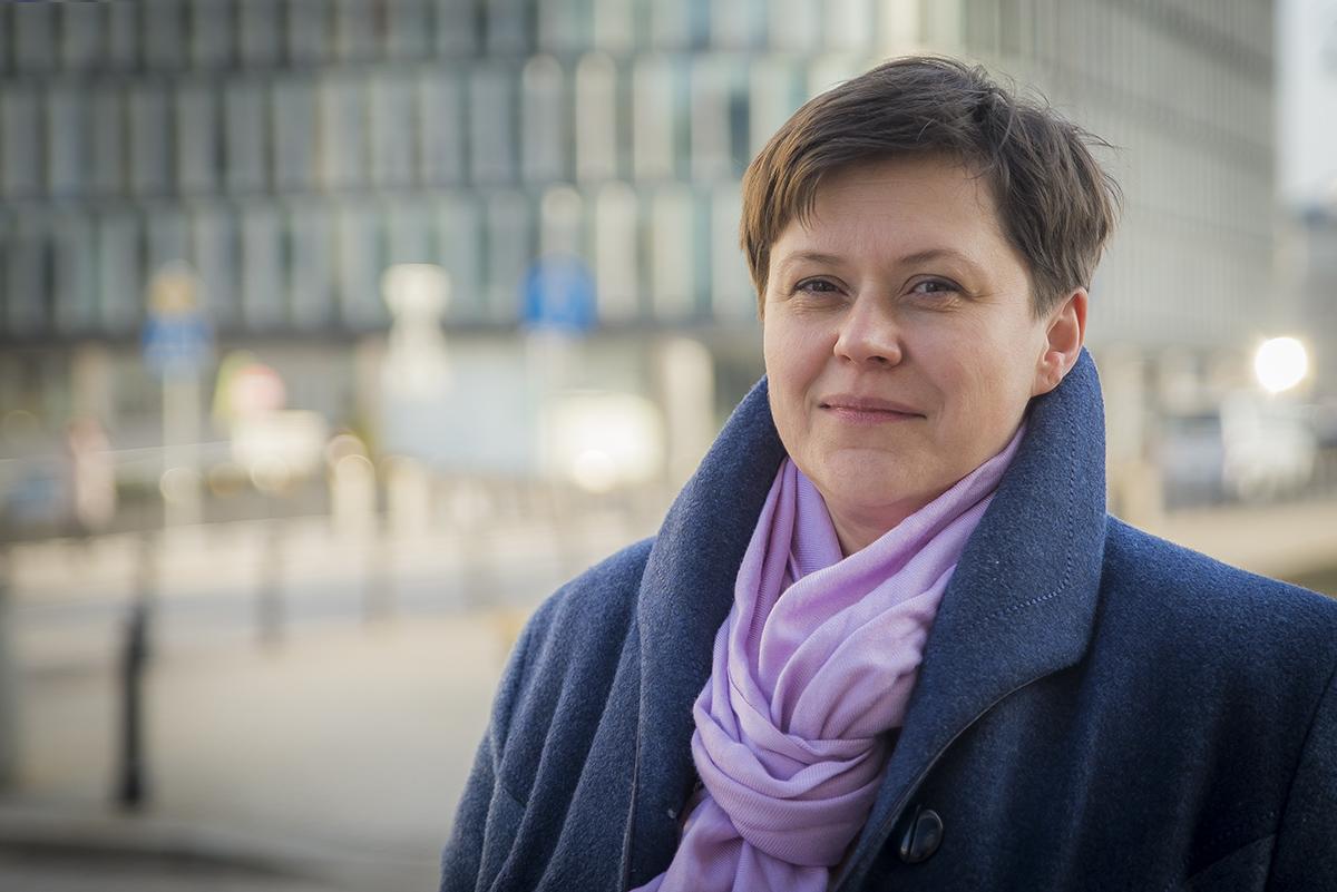 Portret Pani Donaty Kończyk, na tle pejzażu miejskiego. Ma na sobie granatowy płaszcz oraz fioletową apaszkę.