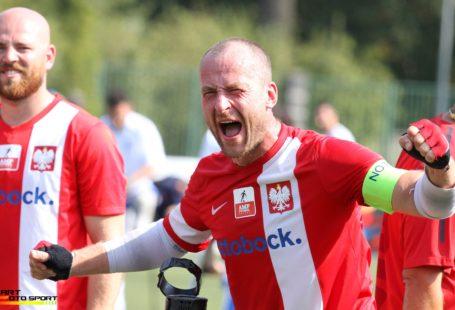 Zdjęcie przedstawia zadowolonych piłkarzy ampfutbolistów w czasie meczu. Ubrani są w czerwone koszulki z białym paskiem z orłem na piersi