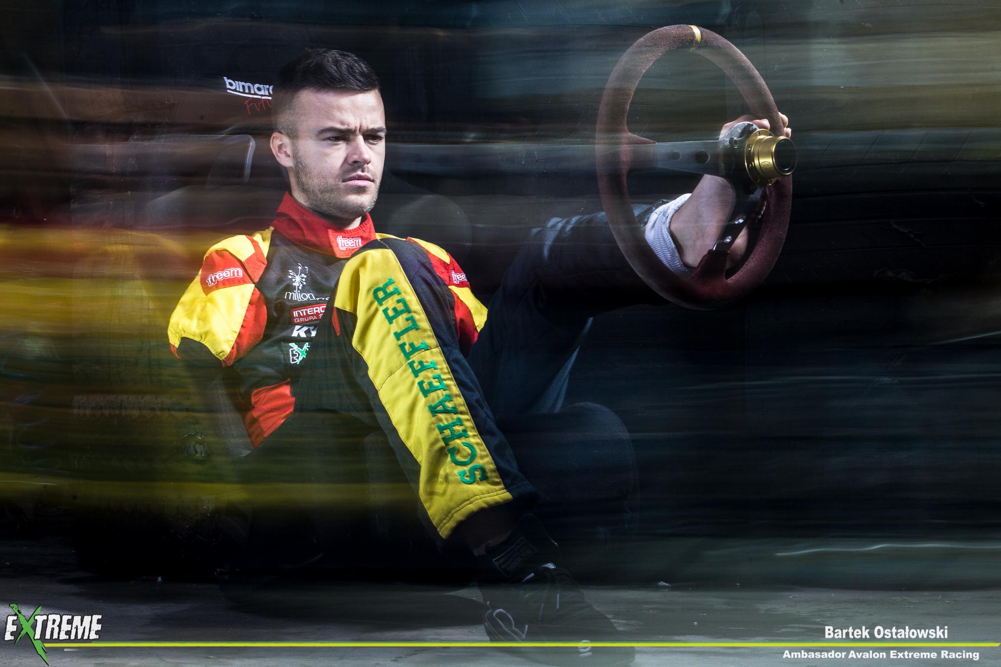 Zdjęcie sesyjne przedstawia Bartka ostałowskiego w czasie prowadzenia samochodu. Kierownicę trzyma lewą nogą, ubrany jest w kombinezon wyścigowy, jest skoncentrowany i skupiony na jeździe. Stylistyka zdjęcia jest dość tajemnicza i mroczna