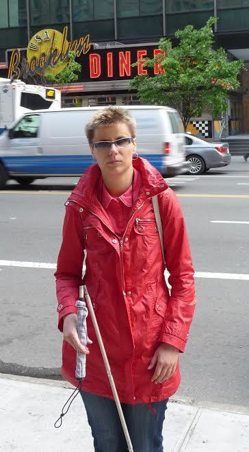 Zdjęcie przedstawia Hanie Pasterny na jednej ze swych podróży, tym razem przed Brooklyn Diner w Nowym Yorku. Ubrana jest w czerwony płaszczyk, na nosie ma ciemne okulary, a w ręku laskę.
