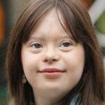 Zdjęcie przedstawia portret uśmiechniętej i pięknej Melanie. Ma piwne oczy i brązowe włosy.