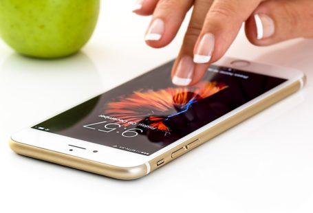 Na zdjęciu widoczna jest dłoń, dotykająca środkowym palcem ekranu smartfona