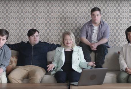 Na zdjęciu widnieje urywek ze spotu, czyli pięć osób (trzech mężczyzn i dwie kobiety) z zespołem downa siedzących na kanapie i rozmawiających