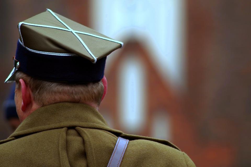 Na zdjęciu widoczny jest żołnierz, stoi obrócony tyłem do zdjęcia