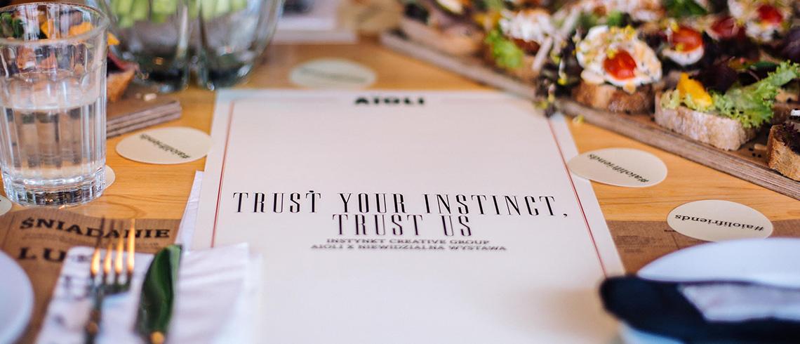 zdjęcie przedstawia leżące na stole menu w brajlu, na którego froncie napisane jest, w języku angielskim: trust your instinct, trust us, a wokół stoją szklanki, leżą sztućce oraz kanapki