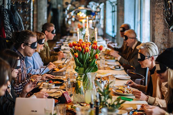 Na zdjęciu znajduje się długi, pięknie udekorowany i suto zastawiony stół oraz siedzący przy nim goście, spożywający posiłek, z czarnymi opaskami na oczach