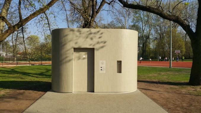 automatyczna toaleta publiczna stojąca w warszawie, jest jasna o obłych kształtach, w oddali drzewa i boisko