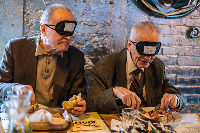 dwóch mężczyzn spożywających posiłek z zakrytymi czarnymi opaskami oczami