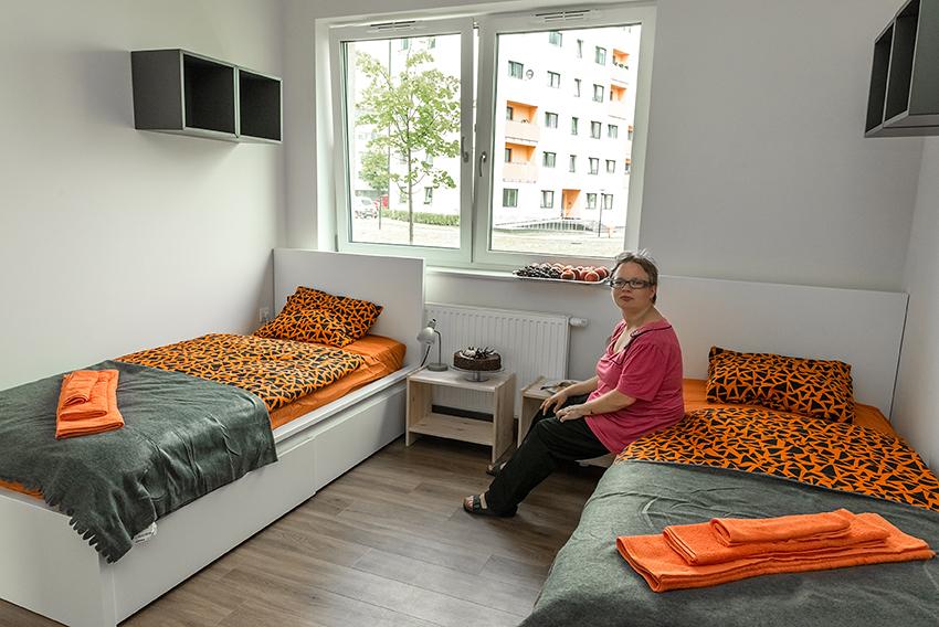 Zdjęcie przedstawia wnętrze mieszkania treningowego, tutaj sypialnię, jest biała, na podłodze ułożone są ciemne panele, na środku duże okno, po dwóch jego stronach stoją białe łóżka jednoosobowe z piękną kolorową pościelą, na jednym z nich siedzi zadowolona podopieczna, obok każdego z łóżek znajduje się drewniana szafka nocna, a nad nimi wiszą szare regały. Jest przytulnie i schludnie.