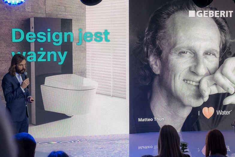 na zdjęciu znajduje się mężczyzna z mikrofonem w trakcie trwania konferencji geberit show. Ubrany jest w garnitur. Za nim znajduje się duży plakat ze zdjęciem łazienki z podpisem Design jest ważny, oraz obok portret Matteo Thuna z podpisem I (rysunek serduszka) water