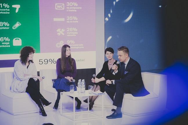 Zdjęcie przedstawia debatę dziennikarzy i architektów. Są to trzy kobiety i jeden mężczyzna. Siedzą na sofach, każdy z nuch trzyma mikrofon. Na małym stoliczku pośrodku znajdują się butelki z wodą oraz szklanki. Każdy ubrany jest oficjalnie.