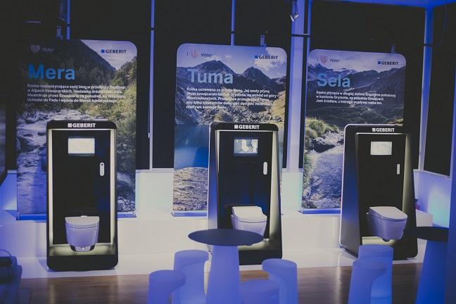Zdjęcie z konferencji przedstwia trzy nowoczesne klozety ustawione obok siebie, Mera, Tuma i Sela