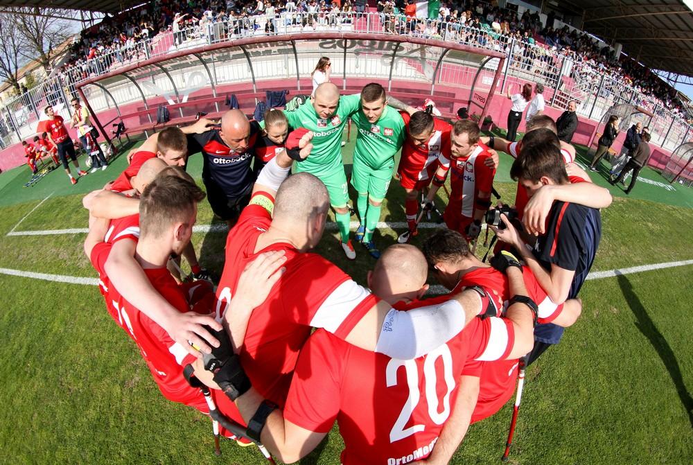 Zdjęcie przedstawia cieszących się z wygranej piłkarzy polskich po meczu z włochami. Trzymają się nawzajem za barki i ramiona tworząc okrąg. Bramkarze ubrani są na kolor seledynowy, a reszta grupy na czerwono