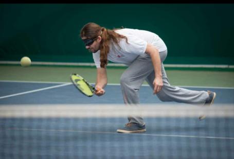na zdjęciu znajduje się mężczyzna z zasłoniętymi czarną opaską oczami grający w tenisa