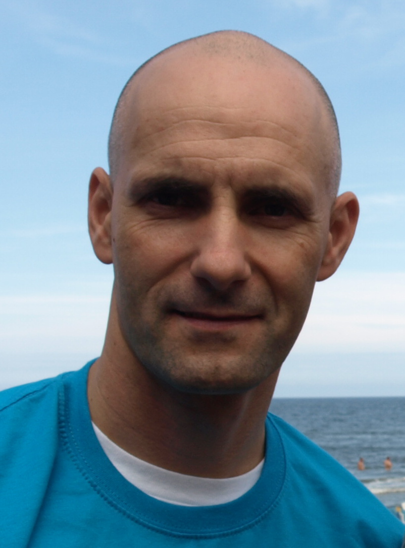 Portret Tomasza Golloba. Ma na sobie niebieską koszulkę, a w tle widoczne jest morze,