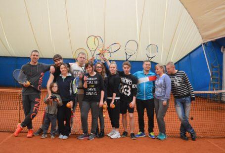 Zdjęcie przedstawia grupę młodych niewidomych tenisistów (kobiety oraz mężczyźni) pozujących do zdjęcia przy siatce, uśmiechających się i trzymający w dłoniach rakiety oraz pomarańczowe piłeczki
