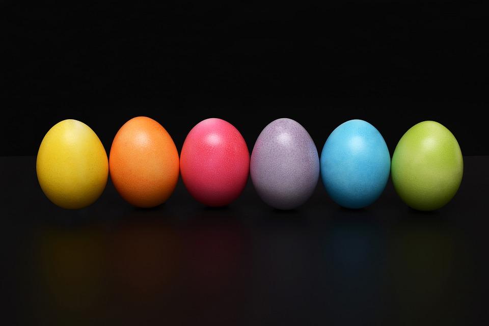 na zdjęciu widocznych jest sześć kolorowych jajek wielkanocnych, na czarnym tle. Są poukładane w jeden ciągły rząd. Każde z nich ma inny kolor, od lewej; żółte, pomarańczowe, różowe, fioletowe, niebieskie i zielone