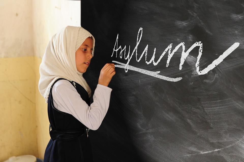 Dziewczynka w wieku około 11 lat, z białą chustą na głowie, pisząca na tablicy słowo asylum