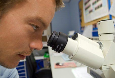 Zdjęcie przedstawia zbliżenie na twarz naukowca patrzącego w mikroskop. Mężczyzna jest młody, lekko się uśmiecha. Ma na sobie biały fartuch