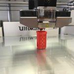 Drukarka 3D w czasie pracy, drukująca przykładowy wzór, tytaj akurat czerwony komin zabawkę